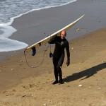 Paul carrying his longboard like a crucifix
